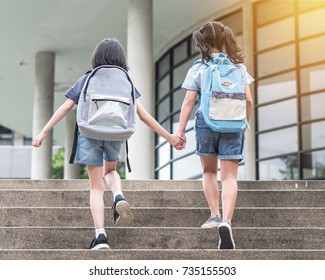 Back to school education concept with girl kids (elementary students) carrying backpacks going to class on school first day holding hand in hand together walking up building stair happily