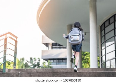 Back to school education concept with kid (elementary student girl) carrying backpacks going, running to class on new academic year first day, walking up to office of admission building stair happily