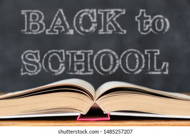 Back to School. Education concept with open book on wooden school desk against the school blackboard background