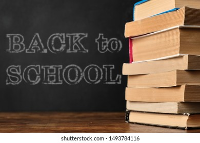 Back to School. Education concept with stack of books on wooden school desk against the background of the blackboard