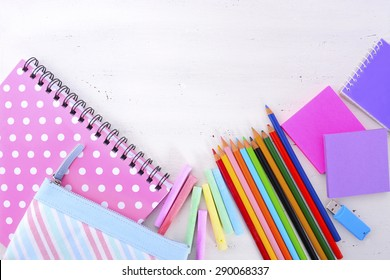 Back to School or Education Concept with stationery and desk accessories overhead on white wood rustic table with copy space for your text here.