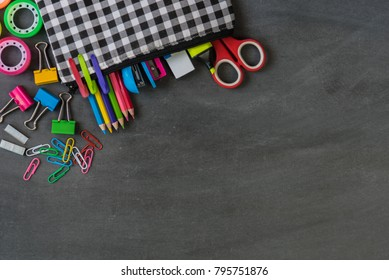 Back to school education concept, school supplies stationery equipment in the bag on wooden backboard or chalkboard for student with copy space.
