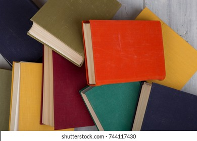 Back to school and education concept - top view of heap colorful hardback books on white wooden table