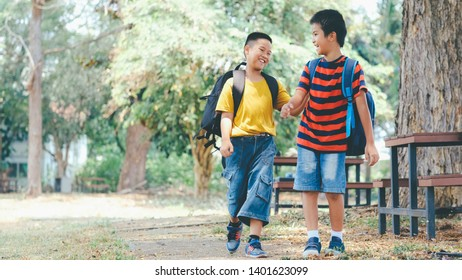 Back to school and education concept. Two boys of primary with school bags behind the back. Little first graders.