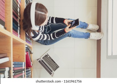Back to school education knowledge college university concept, Female student study in library using tablet and searching internet while Listening music and lessons on white headphones