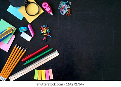 Back to school education supplies concept. Multicolored stationary office equipment on black blackboard background. Copy space. Place for text.