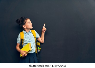 Back to school. enthusiastic girl in uniform with backpack and book in her hand, pointing up, poses on black background. Back to school. copy space. Preparing for school, on background chalkboard.