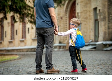Back to school. Father and son go hand in hand. Parent taking child to school. Pupil of primary school go study with backpack. Beginning of lessons.  First day of fall.