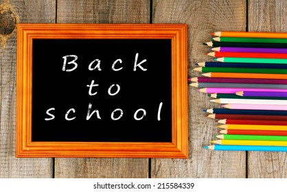 Back to school. Frame and pencils. Vertically. A wooden background.