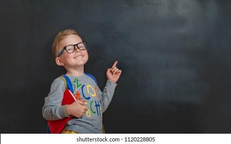 De volta à escola. Garotinho engraçado de óculos apontando para o quadro negro. Criança da escola primária com livro e bolsa. Educação.