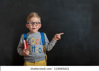 Back to school. Funny little boy in glasses pointing up on blackboard. Child from elementary school with book and bag. Education. Kid with a book