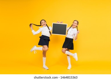 Back to school. Happy children holding school blackboard on yellow background. Little girls preparing for school lesson. Small kids smiling in school uniform on september 1, copy space.