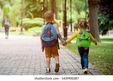 Back to school. Happy children ready for primary school. Pupil on first day of classes. Boy and girl in glasses with backpack and book on backyard. Education for kindergarten and preschool kids.
