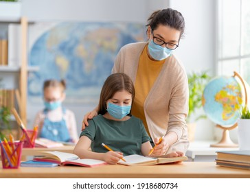 Back to school. Happy children are wearing facemasks sitting at desks. Girls with teacher in classroom.