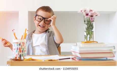 Back to school! Happy cute industrious child is sitting at a desk indoors. Kid is learning in class. Sleepig student