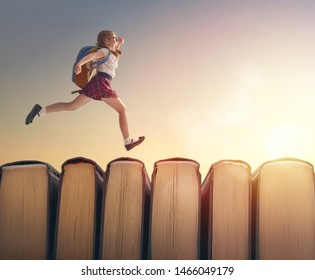 Back to school! Happy cute industrious child are running on books on background of sunset landscape. Concept of education and reading. The development of the imagination.