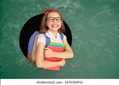Back to school! Happy cute industrious child indoors. Kid in class on background of chalkboard.