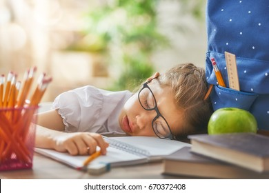 Back to school! Happy cute industrious child is sitting at a desk indoors. Kid is learning in class. Girl is tired and sleeps.