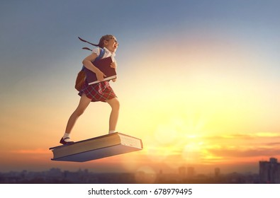 Back to school! Happy cute industrious child flying on the book on background of sunset urban landscape. Concept of education and reading. The development of the imagination.