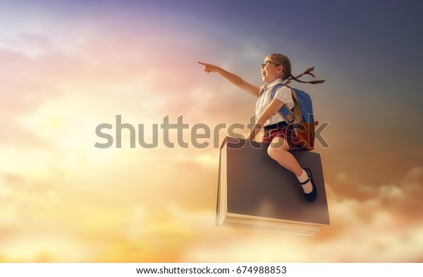 Back to school! Happy cute industrious child flying on the book on background of sunset sky. Concept of education and reading. The development of the imagination.