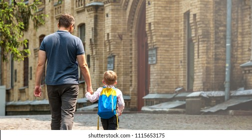 Back to school. Happy father and son go to elementary school. Parent taking child to primary school. Pupil go study with backpack. Beginning of lessons. First day of fall.