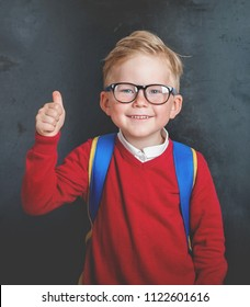 Back to school. Happy little boy in glasses with thumb up and backpack against blackboard.