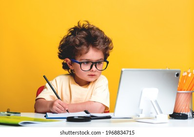 Back to school. Happy little pupil drawing at the desk. Child doing homework with tablet computer. Alarm clock, pencils, books. Kid boy from primary school. first day of fall.
