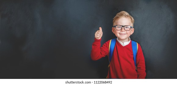 Back to school. Happy smiling boy with thumb up. Child from elementary school in uniform. Kid indoors of the class room with blackboard on a background. Funny kid