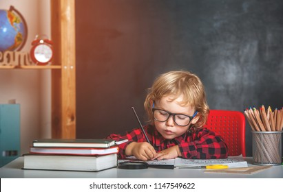 Back to school. Happy smiling pupil drawing at the desk. Child in the class room with blackboard on background. Alarm clock, pencils, books. Kid girl from primary school. first day of fall.