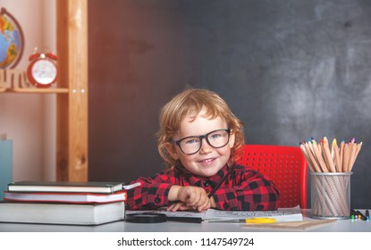 Back to school. Happy smiling pupil sitting at the desk. Child in the class room with blackboard on background. Alarm clock, pencils, books. Kid girl from primary school. first day of fall.