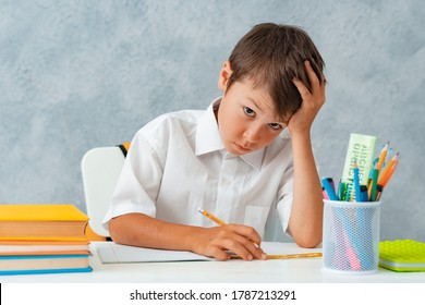 Back to school. Happy smiling student draws at the Desk. A schoolboy solves his homework. A boy from elementary school.