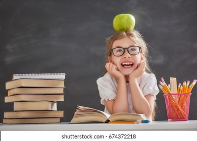 Back to school and happy time! Cute industrious child is sitting at a desk indoors. Kid is learning in class on background of blackboard. Girl reading the book.