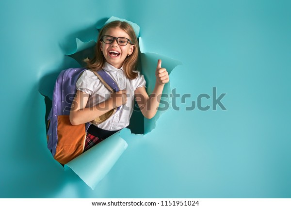 Back to school and happy time! Cute industrious child is breaking through color paper wall. Kid with backpack. Girl ready to study.
