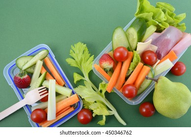Back to school healthy school lunch box on green background with copy space.