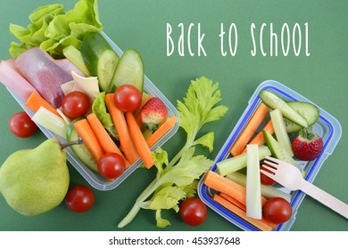 Back to school healthy school lunch box on green background with sample text.