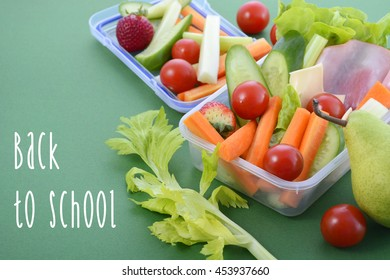 Back to school healthy school lunch box on green background, closeup with sample text.