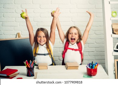 Back to school and home schooling. Happy school kids at lesson in september 1. Friendship of small sisters in classroom at knowledge day. Little girls eat apple at lunch break. School time of girls.