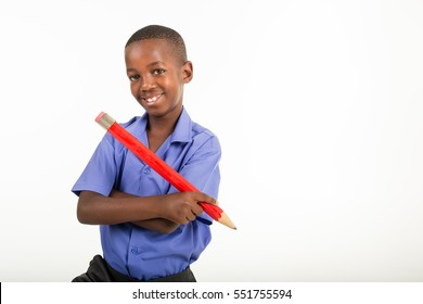 Back to school images of a friendly and good looking black South African child in his school uniform holding a jumbo red pencil.