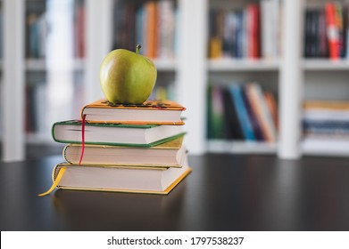 Back to school. Items for the school, books, color pencils and and green apple on a dark wooden table. School supplies on dark board background. Library in background. Back to school concept.