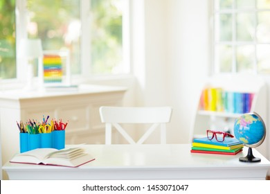Back to school. Kids bedroom with wooden desk, books, globe, backpack, glasses and pencils. White room with big window for young child. Home interior for girl or boy. Table for homework and study.