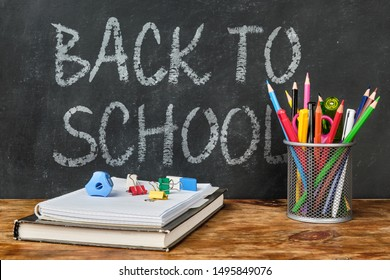 Back to school lettering with school supplies such as textbook, notebook, pens, pencils, scissors and other