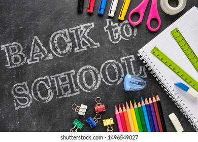 Back to school lettering with school supplies such as ruler, notebook, pens, pencils, scissors on chalkboard