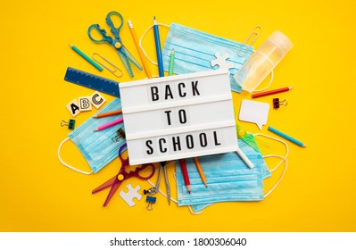 Back to school lightbox message with school equipment and covid masks