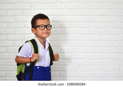 Back to school, little Asian kindergarten boy in school uniform wearing glasses carrying a bag and a notebook ready to go to school, first day to school with copy space for text