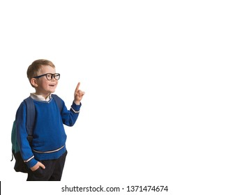 Back to school. Little boy in glasses with bag pointing up on blackboard isolated on white. Child from elementary school. Education.