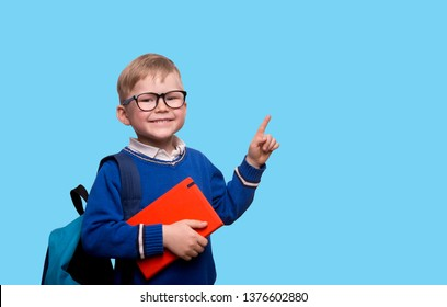 Back to school. Little boy in glasses with bag pointing up on blackboard isolated on blue. Child from elementary school with book. Education.