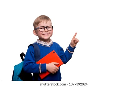 Back to school. Little boy in glasses with bag pointing up on blackboard isolated on white. Child from elementary school with book. Education.