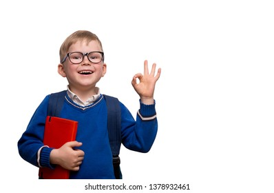 Back to school. Little boy in glasses with bag and book shows OK or alright sign. Success and happy kid isolated on white. Child from elementary school with book. Education.