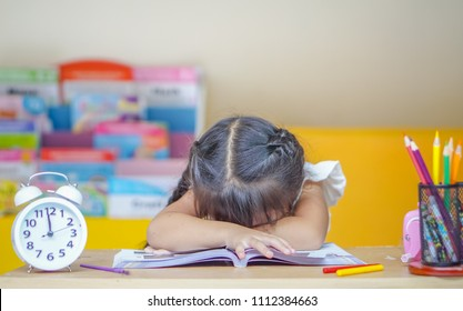 Back to school!. Little girl is sitting at a desk indoors. Girl is tired and sleeps.