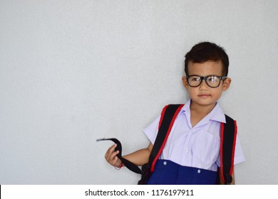 Back to school, little nerdy Asian kindergarten boy in school uniform wearing glasses carrying a bag and a notebook ready to go to school on light grey background, first day to school